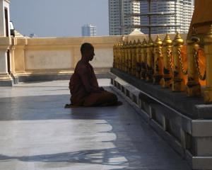 MOnk praying on roof of Wat Saket atop Golden Mount