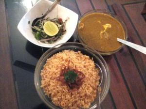 Dhansak served with salad and caramelized rice